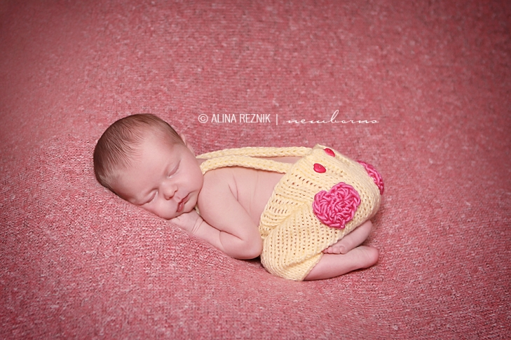 Beatiful baby girl wearing knitted overalls is sleeping while being photographed during her newborn photography session in New York City