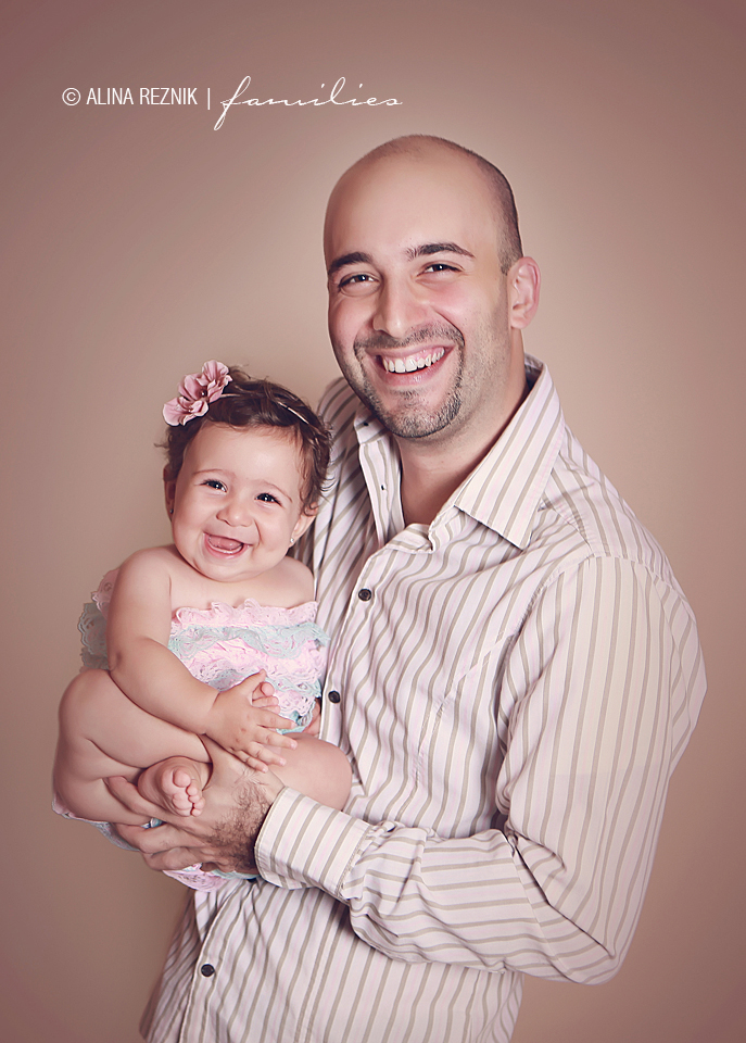 Father and Daughter are smiling during a photography session at Alina Reznik