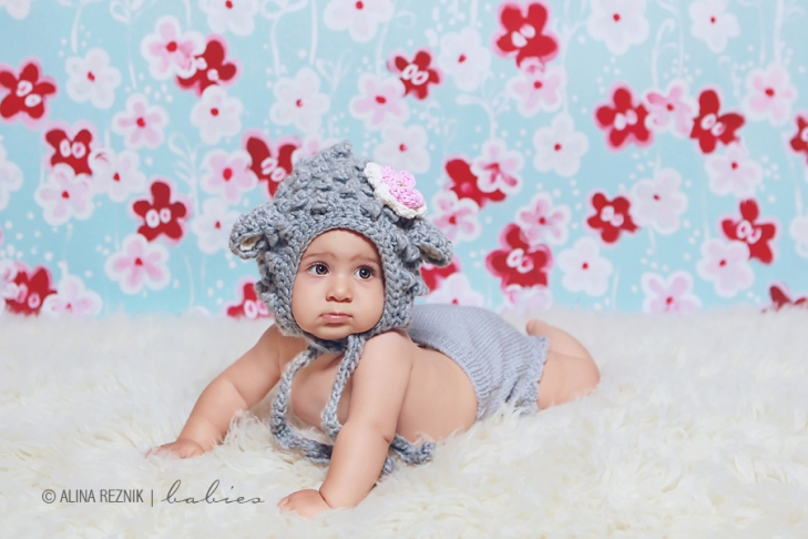 Baby lying on her back wearing a hat with a flower posing for a New York Baby Photographer Alina Reznik
