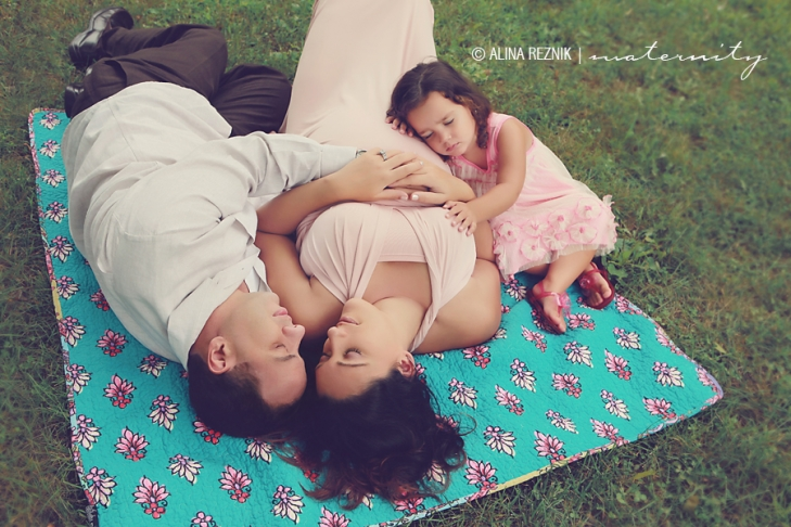 Family lying on a blanket during a maternity photo session in New York City