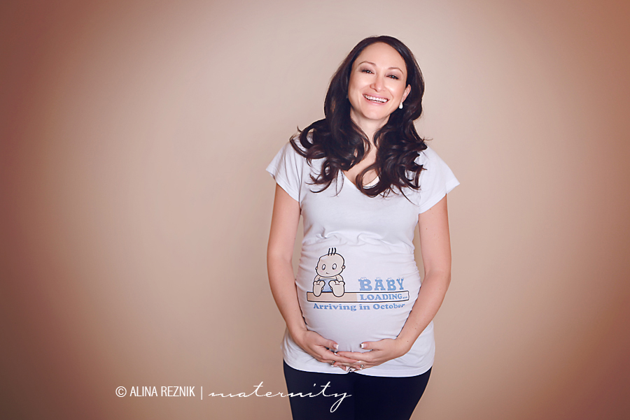 """Pregnant photoshoot in New York where a an expectant mother is smiling at the camera while wearing a """"Baby Loading"""" shirt"""