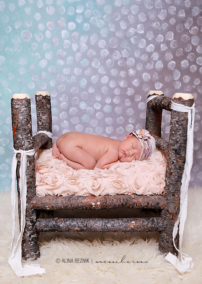 Newborn sleeping in a wooden four post bed while New York based photographer captures her in her sleepy stage