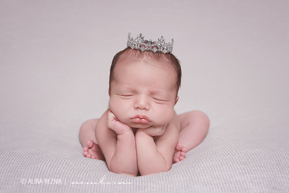 Newborn wearing a silver crown is posed during a newborn photography session in New York City photography studio
