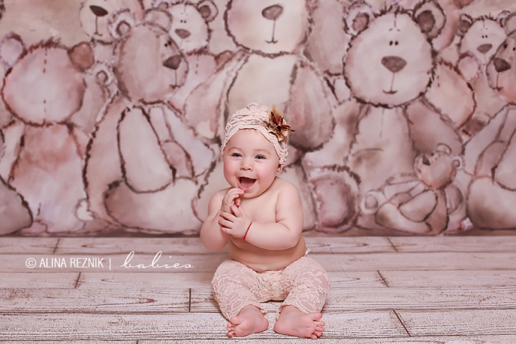 Baby is smilling around a ton of teddy bears as her background.  Photo taken by Alina Reznik during a Baby Photography Session in New York City