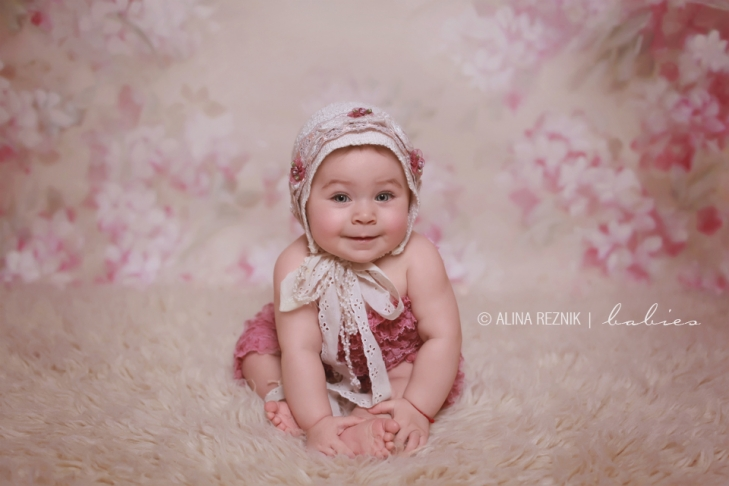 Baby girl smiling at the photographer during a new york baby photography photo shoot.