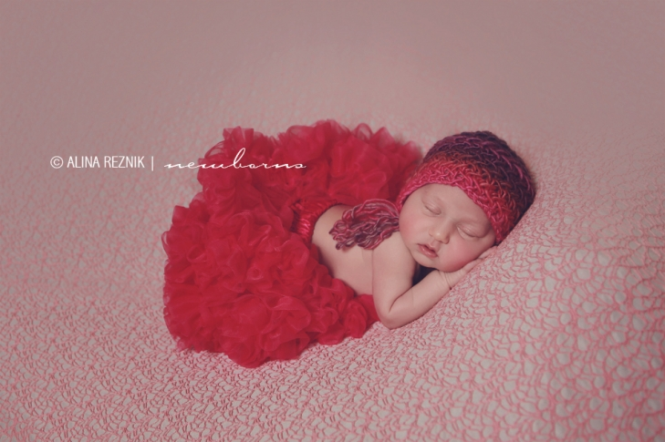 Newborn Baby wearing a bright red tutu and a red knitted hat during a newborn photography session in Brooklyn New York City