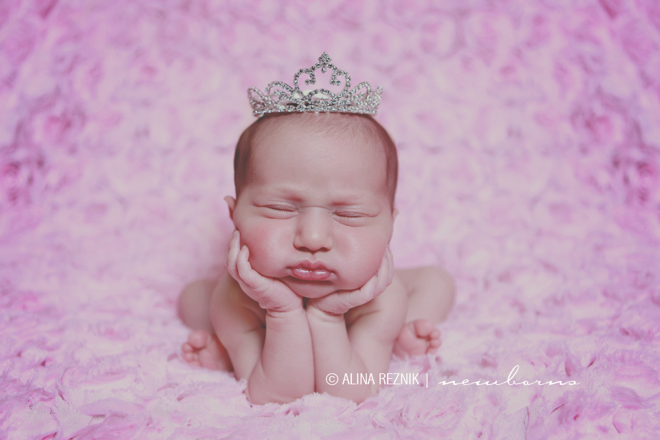A baby is posed wearing a silver crown with hands under his chin during a Brooklyn Newborn Photoshoot in New York City.