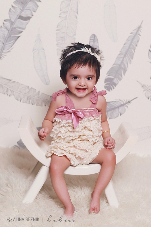 Cute Baby girl is smilling at the camera while being photographed by the Brooklyn New York based photographer Alina Reznik