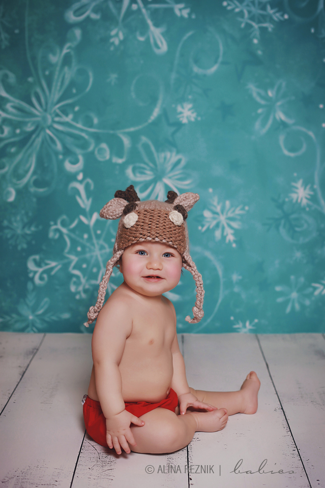 Baby boy wearing a hat with ears smiling while a photo is being taken by his baby photographer in Brooklyn New York