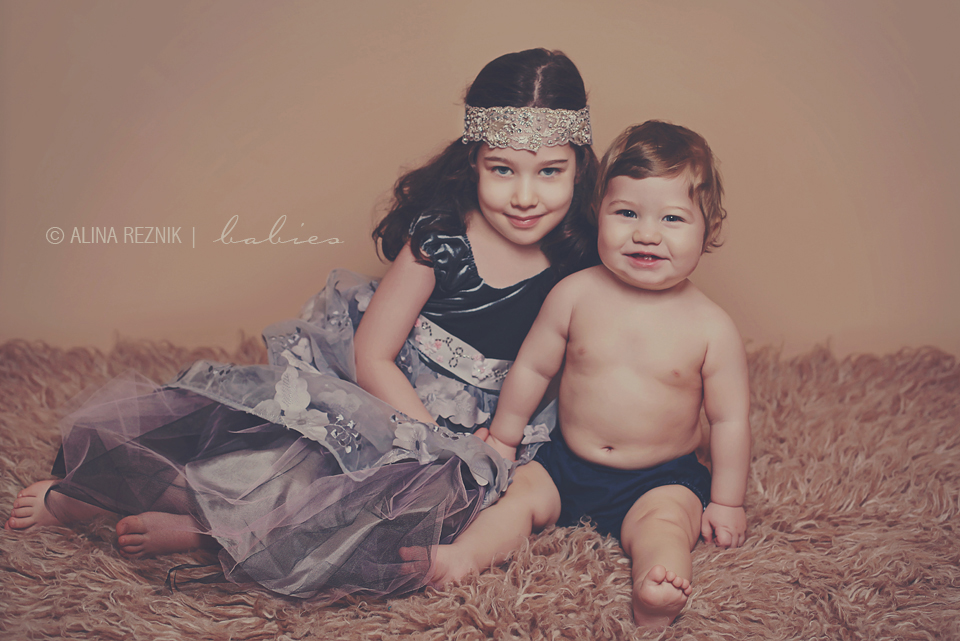 Brother and sister are posed together during a baby photo session in New York City photo studio