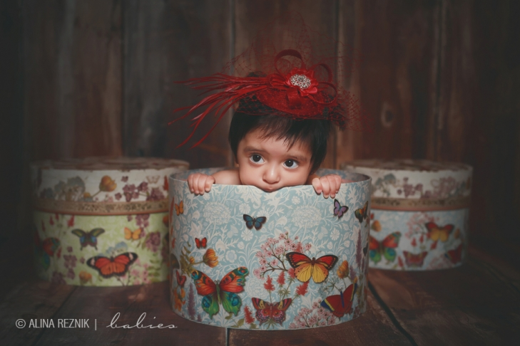 Baby girl is biting on a basket during her brooklyn based photography session