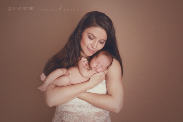 Mother of a newborn baby girl is holding her during a newborn photography session in New York, New York