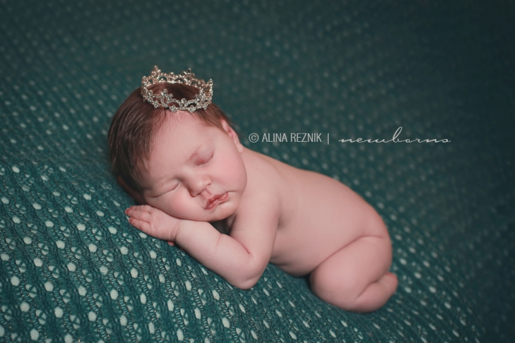 Newborn baby girl wearing a hand made crown posed while sleeping at her newborn photo session in New York