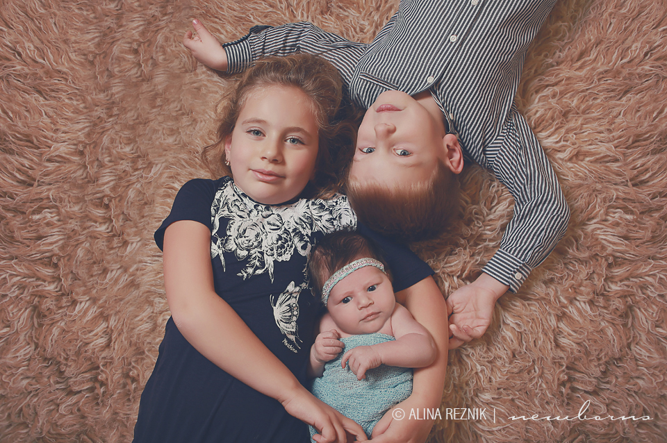 Older Sister and Brother are hugging their new sister during a newborn photography session in New York