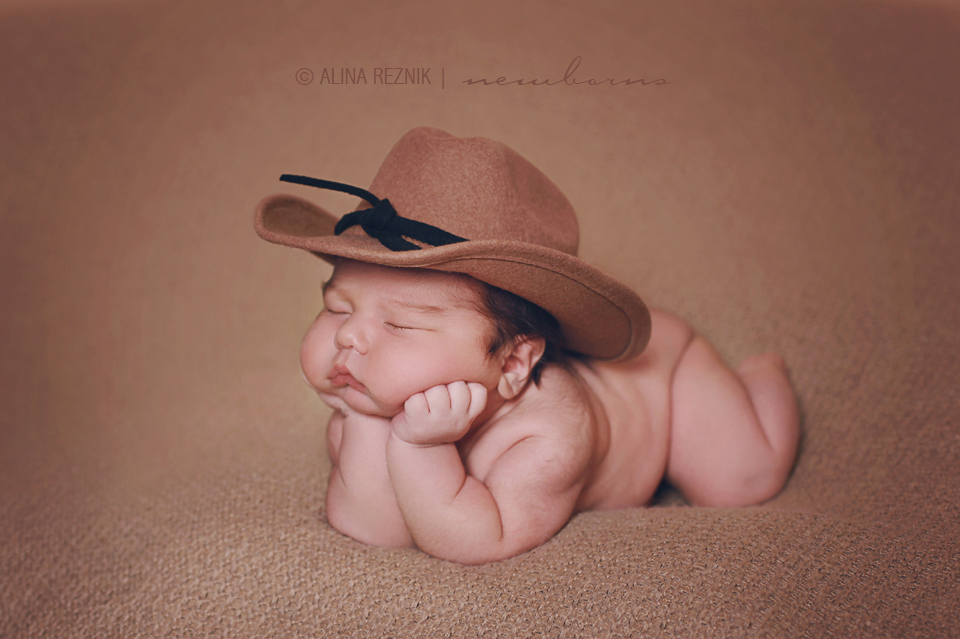 Newborn baby boy posed with hands under the head to keep the head up while wearing a cowboy hat during a photography session by newborn specialist Alina Reznik