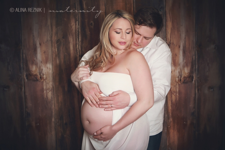 Couple who are expecting their first newborn are posed behind one another during a Maternity Photo Session in Alina